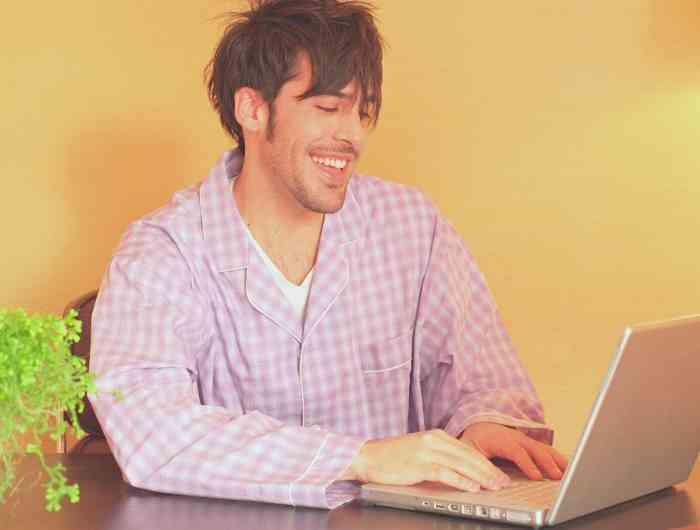 Man wearing pajamas working on computer