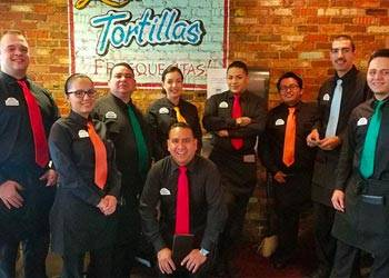 Group of waiters wearing black shirts and colorful solid neckties.
