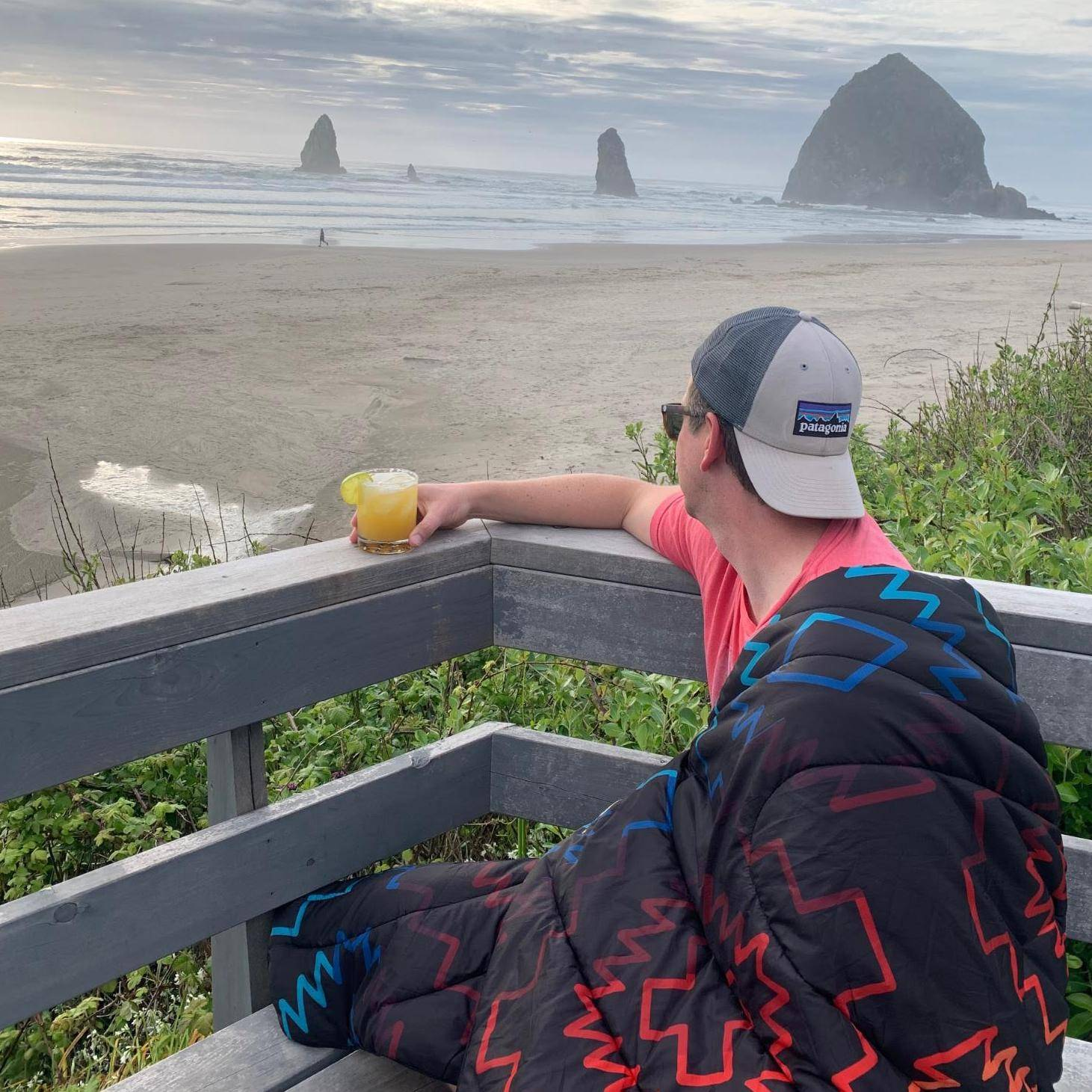 Man drinking margarita at Cannon Beach with Rumpl beach blanket