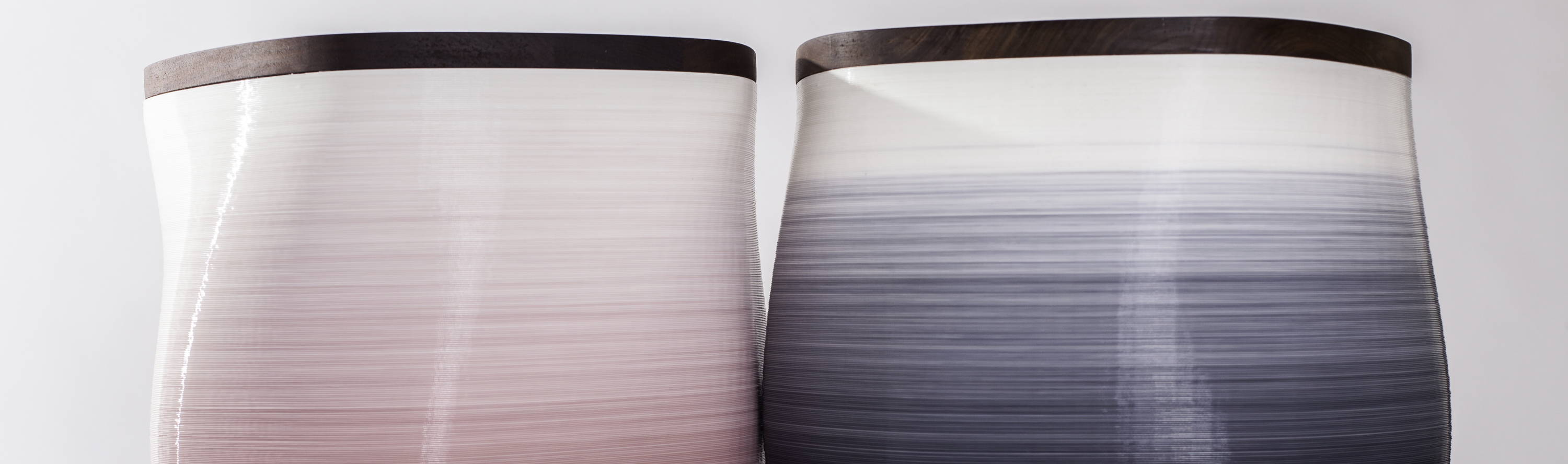 Mauve ombre side table next to black ombre side table made of plant based resin bases and hardwood tops
