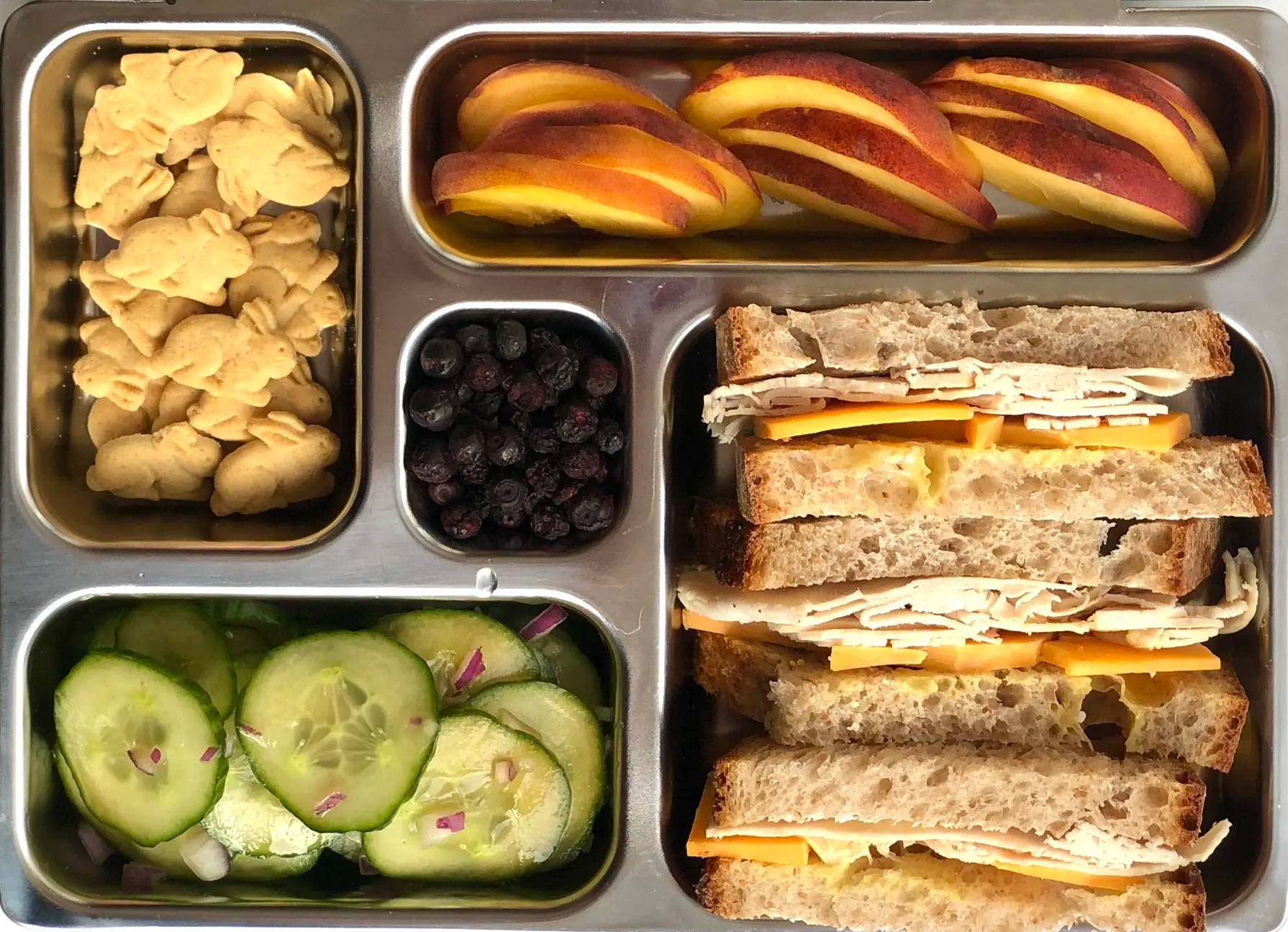 Sneak peek of a kid's quick and healthy school lunch containing Turkey & Cheddar on Sourdough, Quick Cucumber Salad, Sliced Peach, Mini Graham Crackers, and Freeze-Dried Fruit.