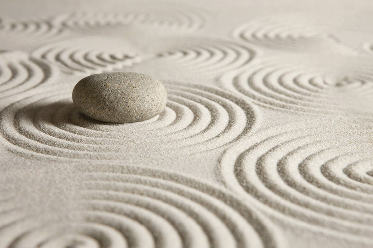 Smooth stone surrounded by sand in a zen garden