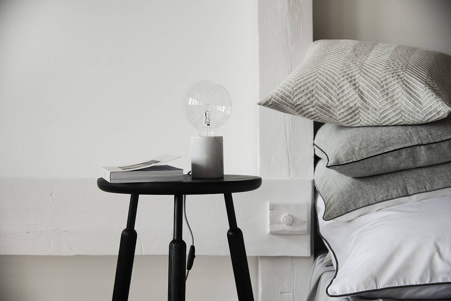 Lagom style interior decor with black side table, edison bulb table lamp and grey scatter cushions
