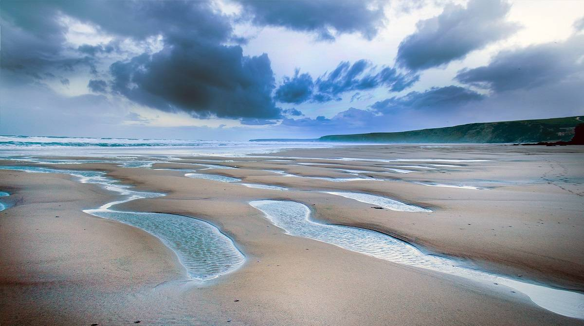 A beach at low tide with dark clouds overhead