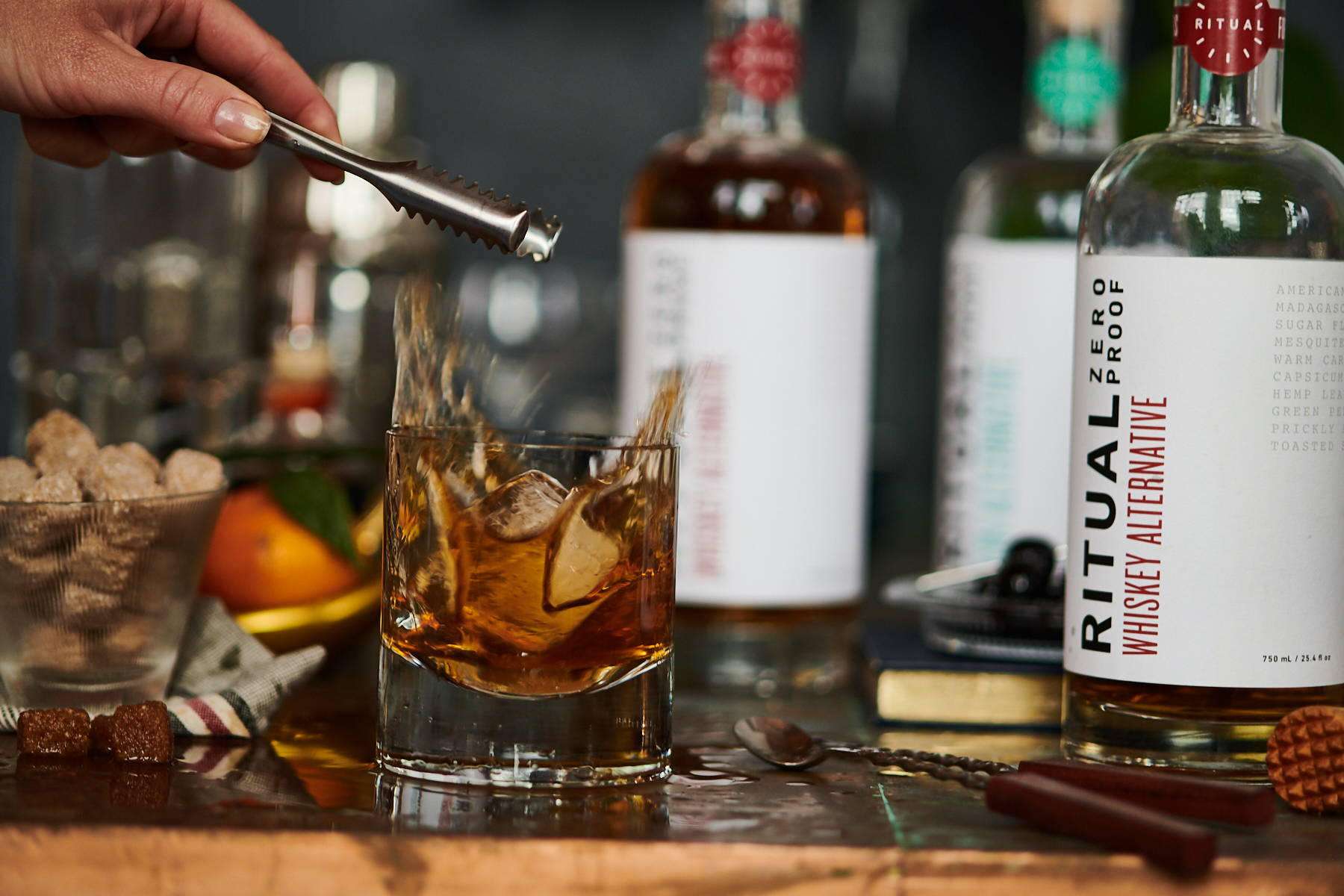 An ice cube dropping into a glass of Ritual spirit-free whiskey alternative, creating a splash, with bar accessories nearby.