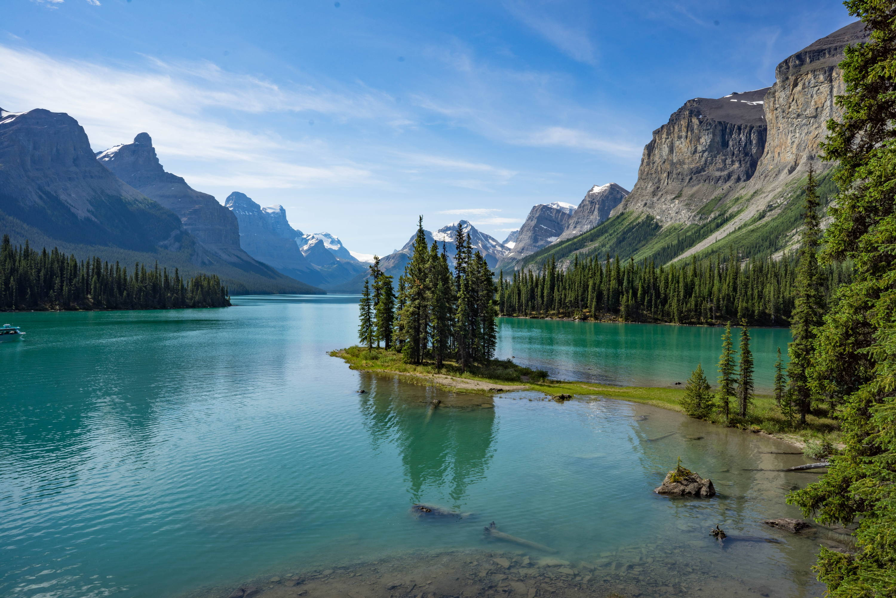 Things to Do in the Canadian Rockies: Island full of pine trees sits awkwardly in a teal-blue lake with mountains surrounding.