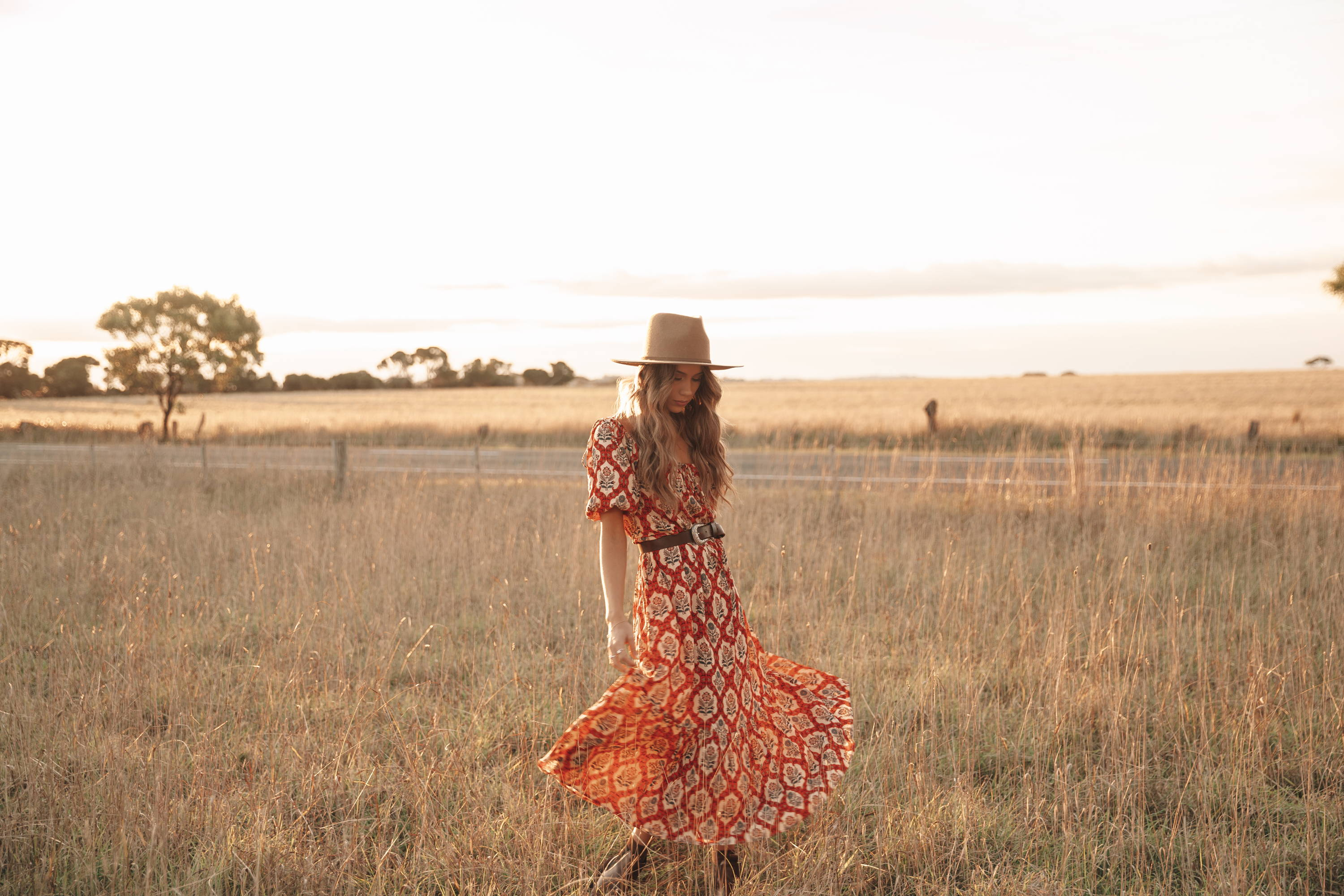 Girl in field wearing red printed boho maxi dress with hat winter style