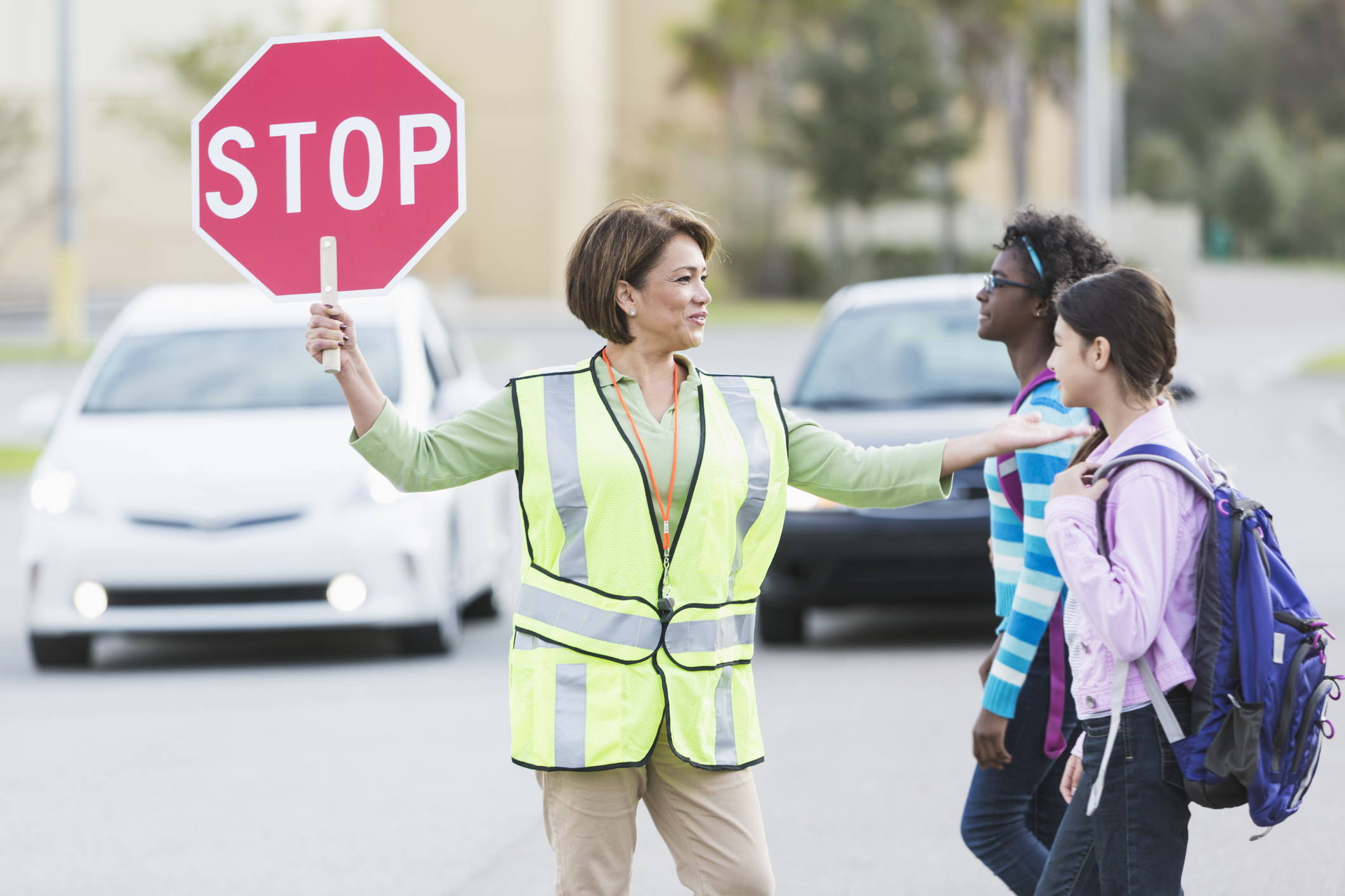 School crossing guard and students using crosswalk