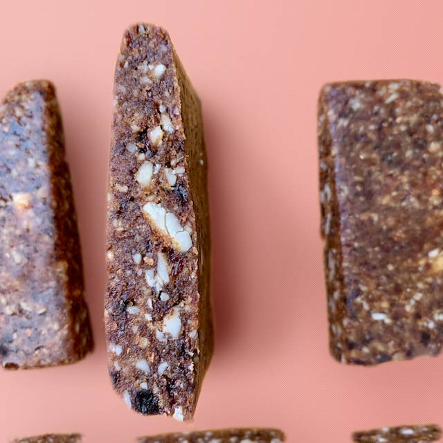 Kid friendly energy bars made of dates, raisins, almonds, cocoa powder, vanilla, and cinnamon.
