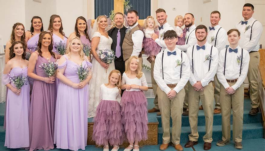 Wedding party wearing dusty blue and lilac purple