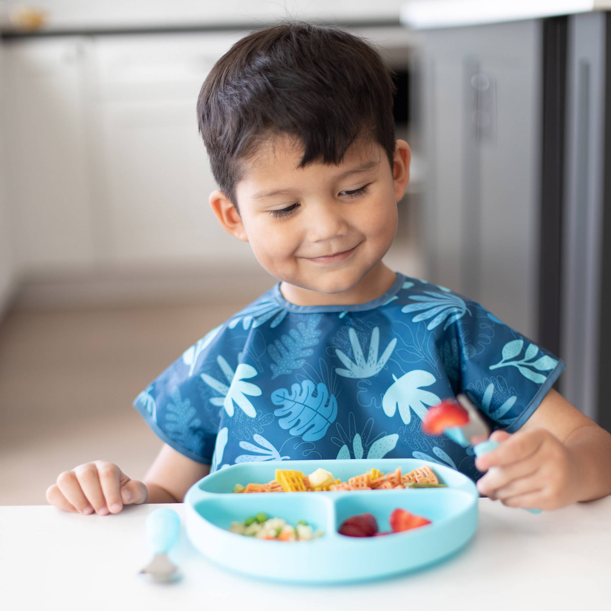 little boy eating lunch in suction plate with bib