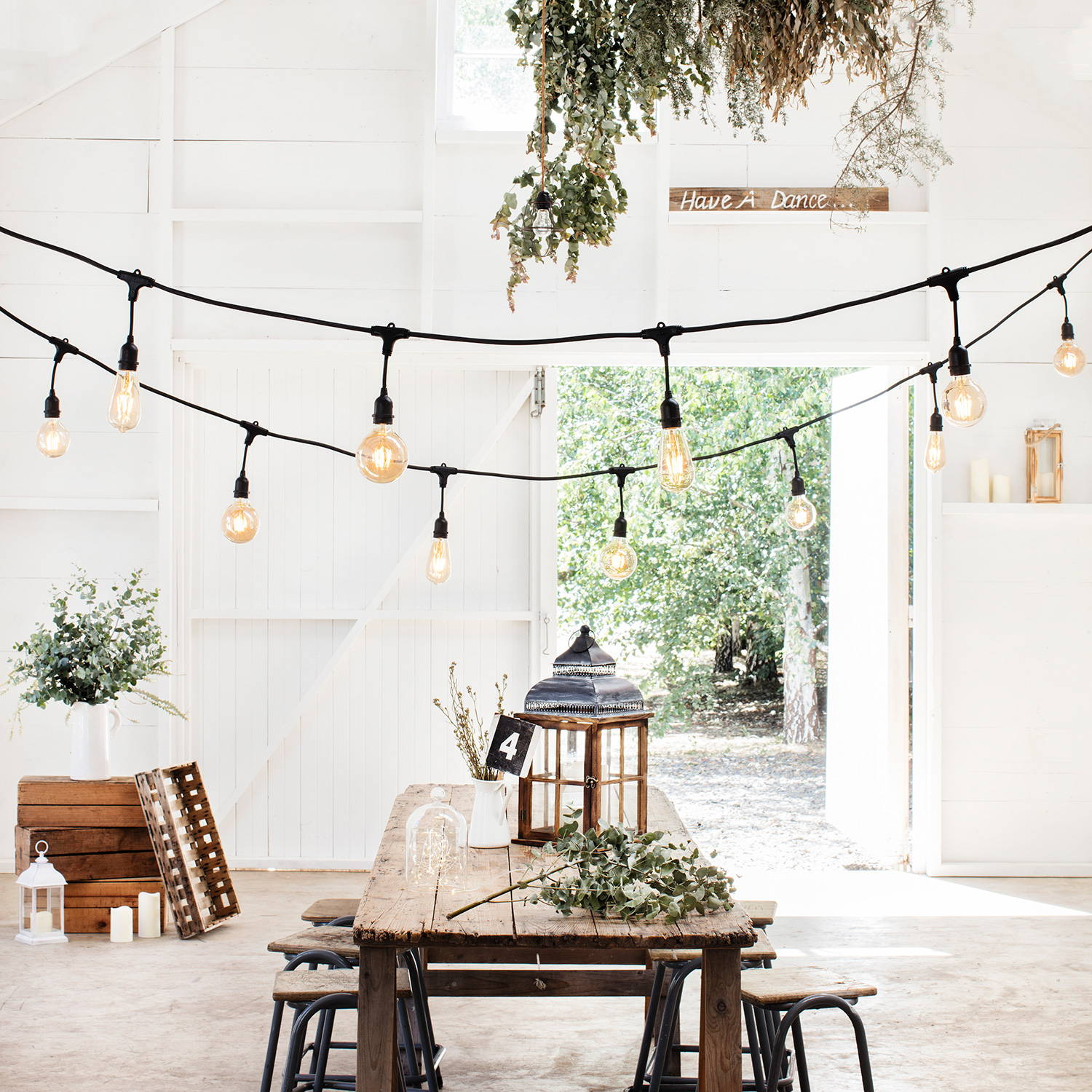 A barn wedding setting with a string of industial style festoon lights