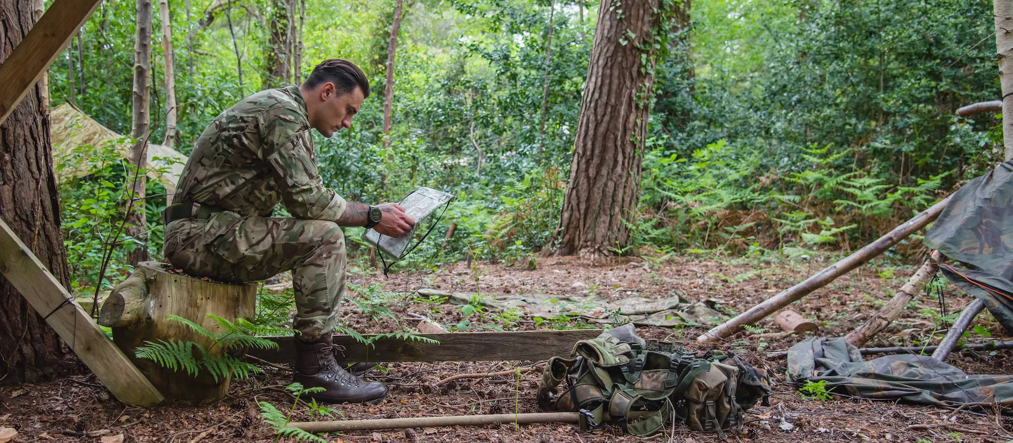 Soldier wearing a Garmin military GPS smartwatch at camp in the field