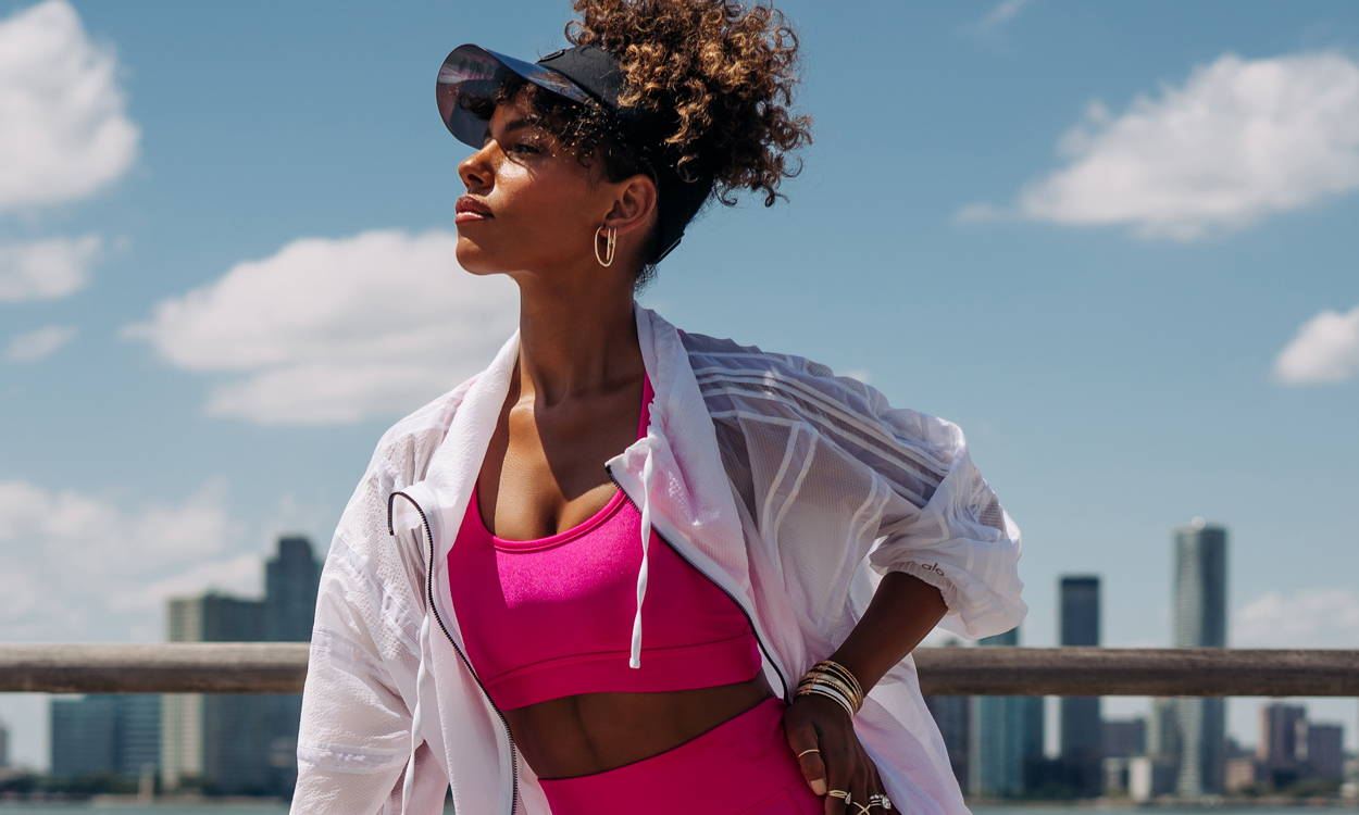 Model stretching riverside wearing workout clothes and Ring Concierge jewelry