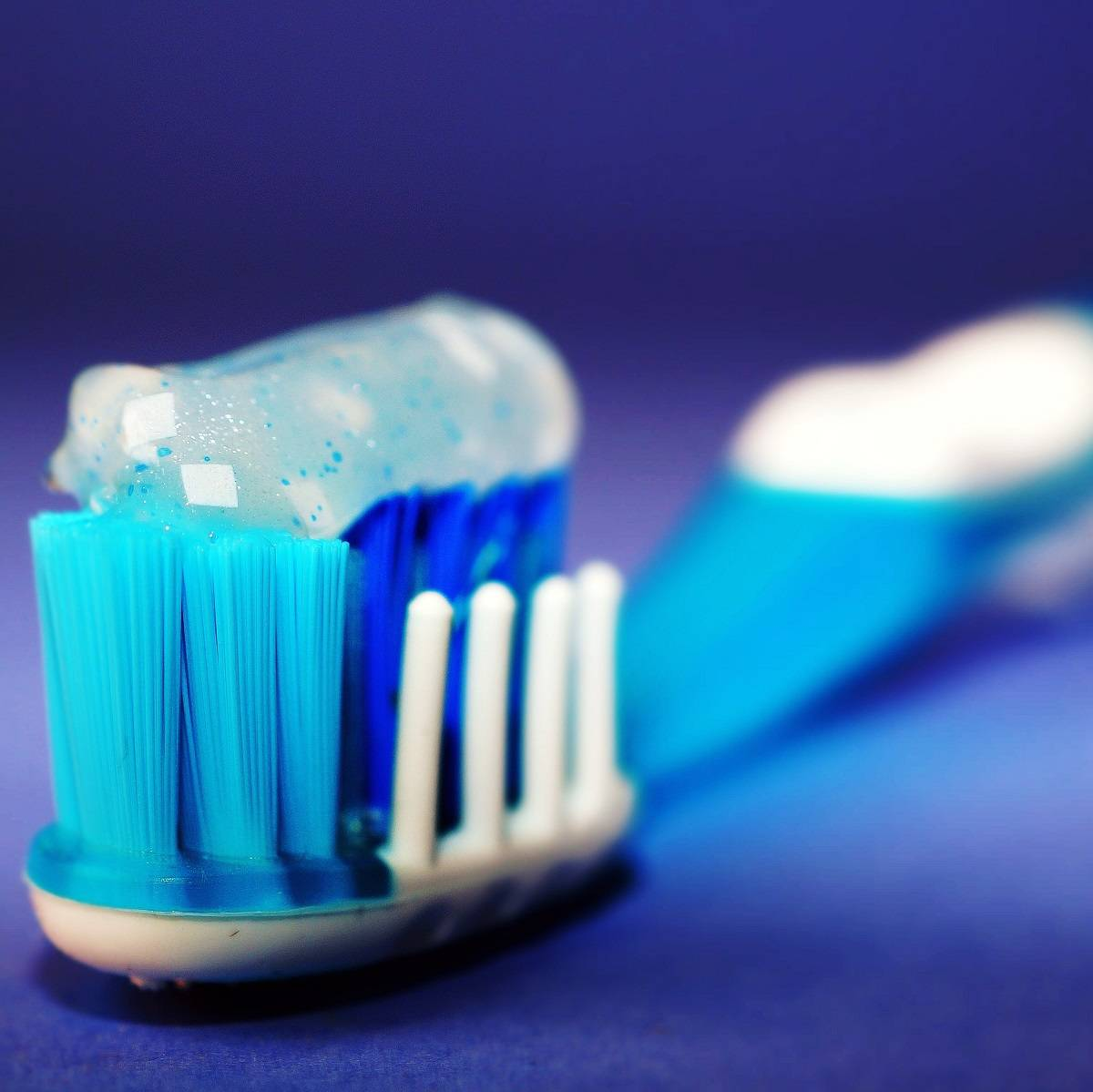 White and blue toothbrush with toothpaste