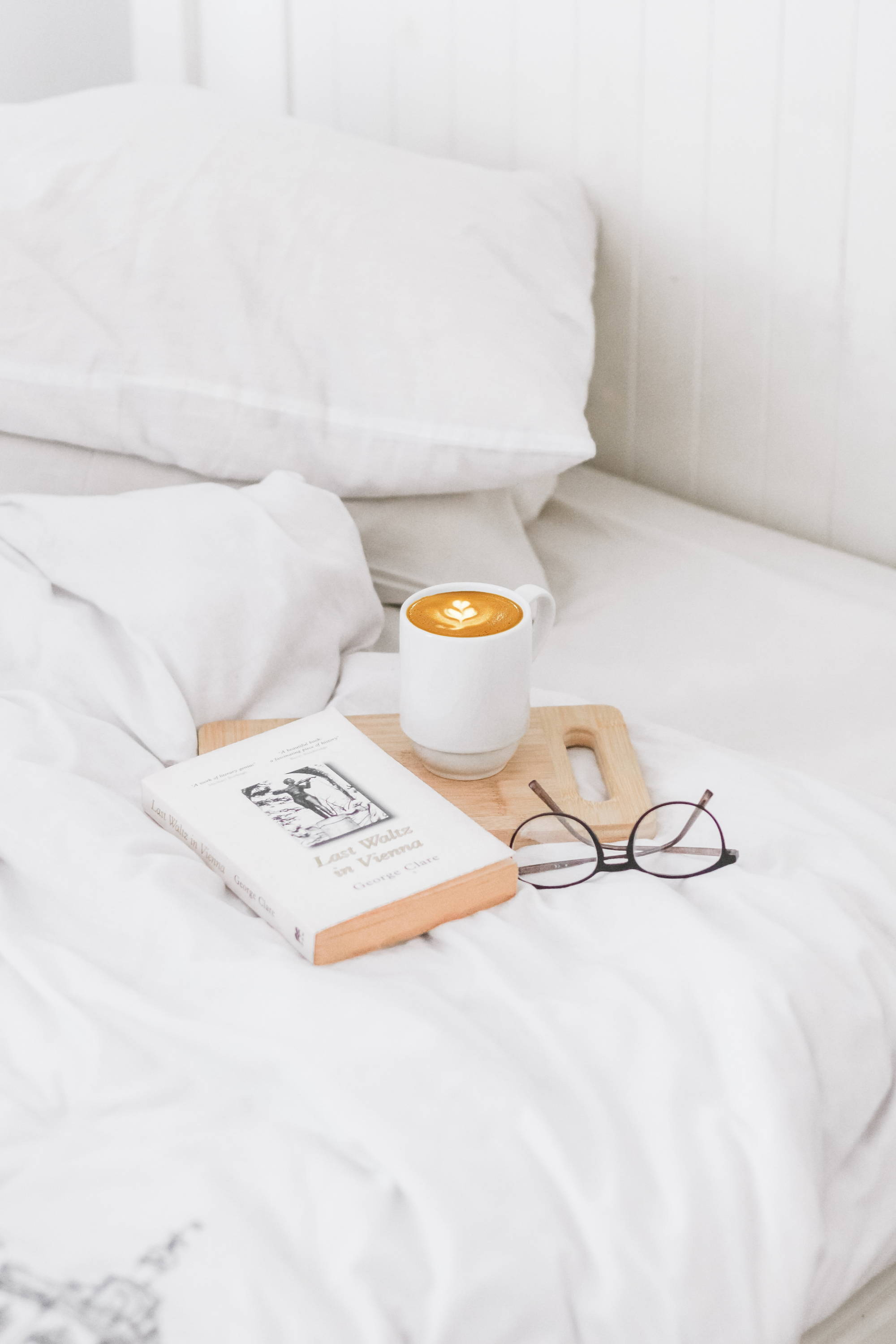 A cup of coffee, book, and reading glasses on a bed with eucalypso eucalyptus sheets