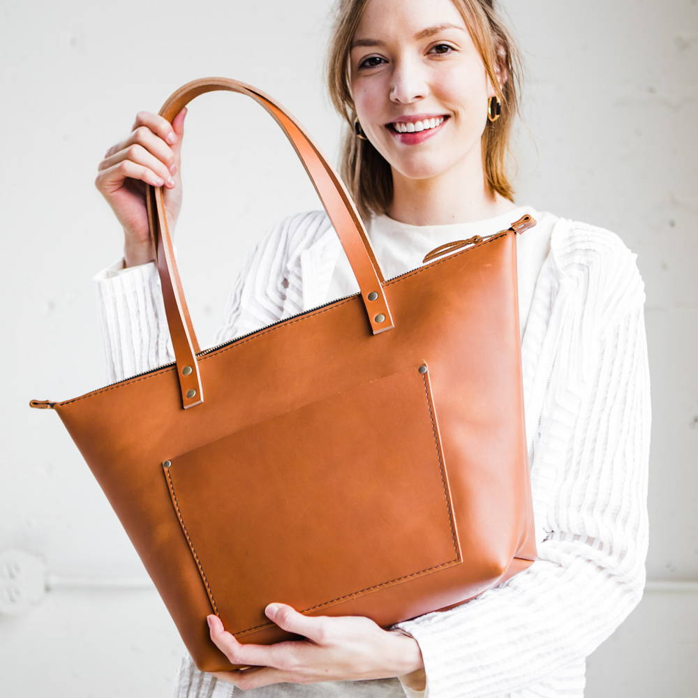 smiling woman holding a handmade leather zipper tote bag by portland leather goods