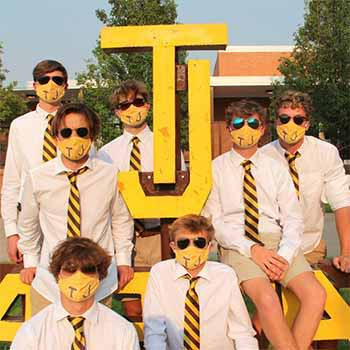 Students wearing school striped ties and matching face masks