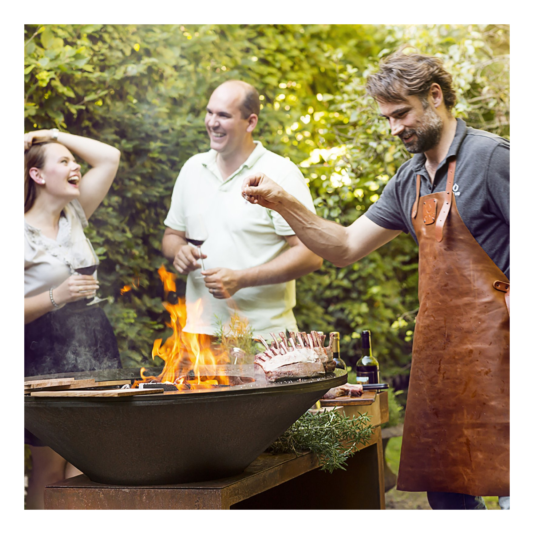 Several guests surround a cook who is grilling over a fire pit grill