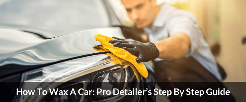 A photo of a professional car detailer. He is wearing an apron and black gloves. He is putting the finishing touches on a black sedan car. The paint looks smooth like butter.