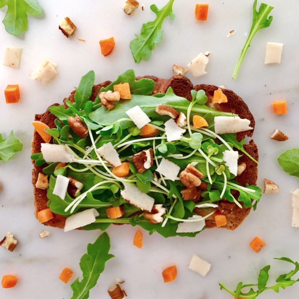 Open face sandwich with arugula, carrots, walnuts, and daikon radish microgreens.