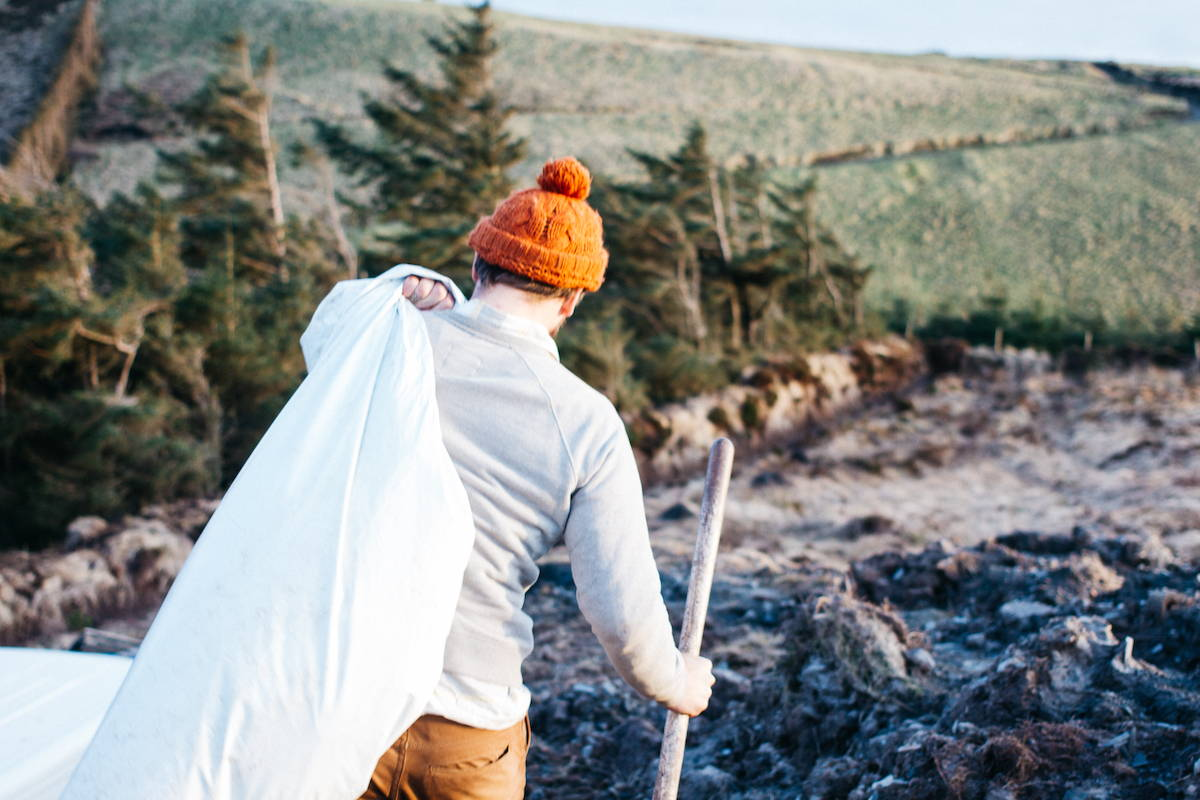 A tree planter carries supplies on a frosty morning at our reforesting Ireland project.