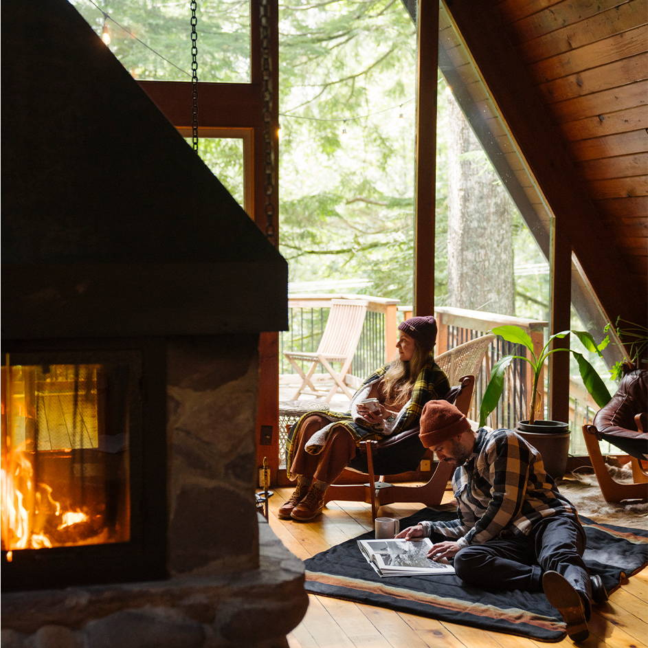 Cuddled up with a blanket and hot cocoa by the fire in a cabin | Rumpl