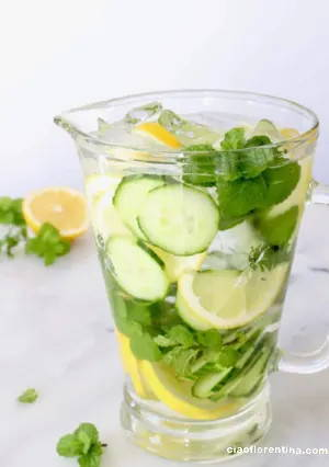 Big jug of water with lemons, cucumber and mint leaves