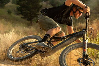 An electric mountain bike using tons of speed and torque turning a corner off road.