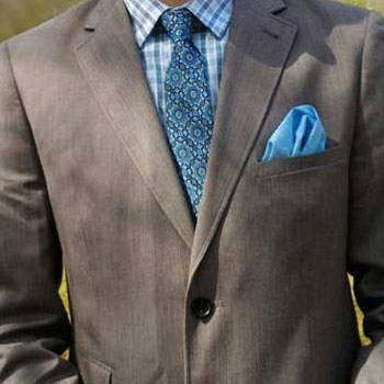 Customer wearig a blue pattern tie and a pocket square