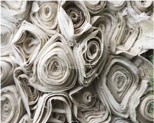 Pile of undyed natural fabric stacked on top of one another by Ethan Bodnar on Unsplash