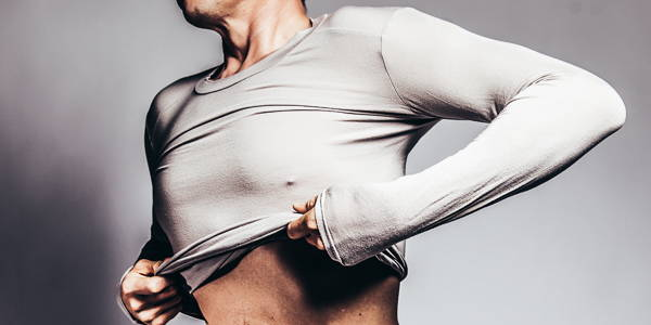 Picture of man pulling on grey sports undershirt
