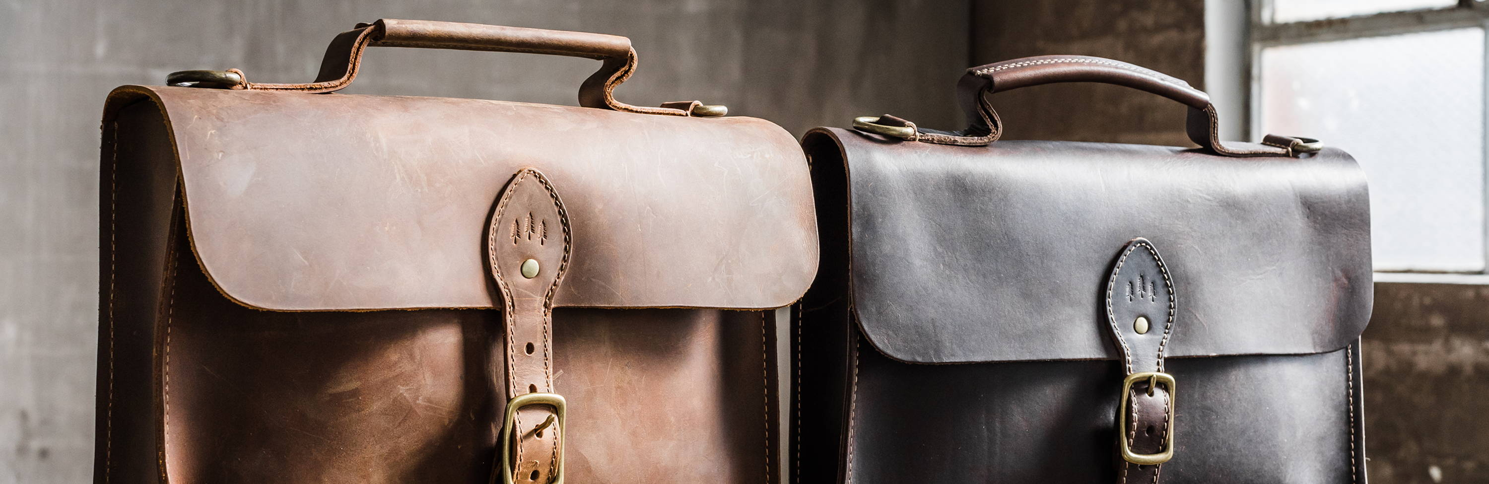 two handmade leather attache bags in black and grizzly leather by portland leather goods