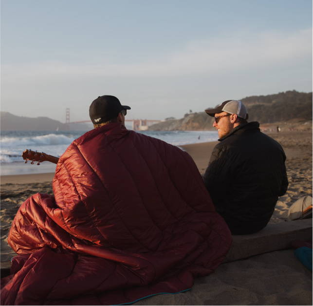 Two friends sitting on the beach wrapped in a Rumpl blanket