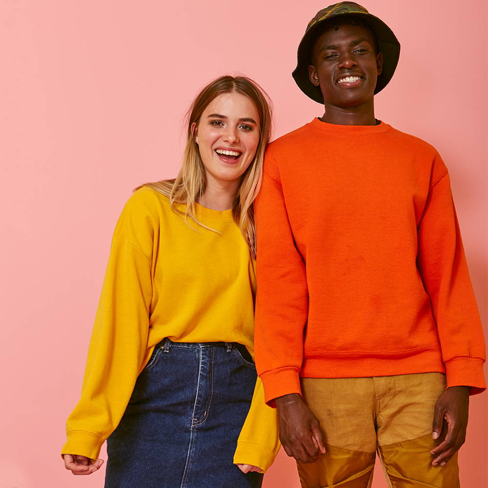 Girl and boy in brightly coloured vintage sweatshirts and denim