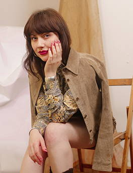 Girl in red lipstick wearing a suede jacket and floral printed vintage dress