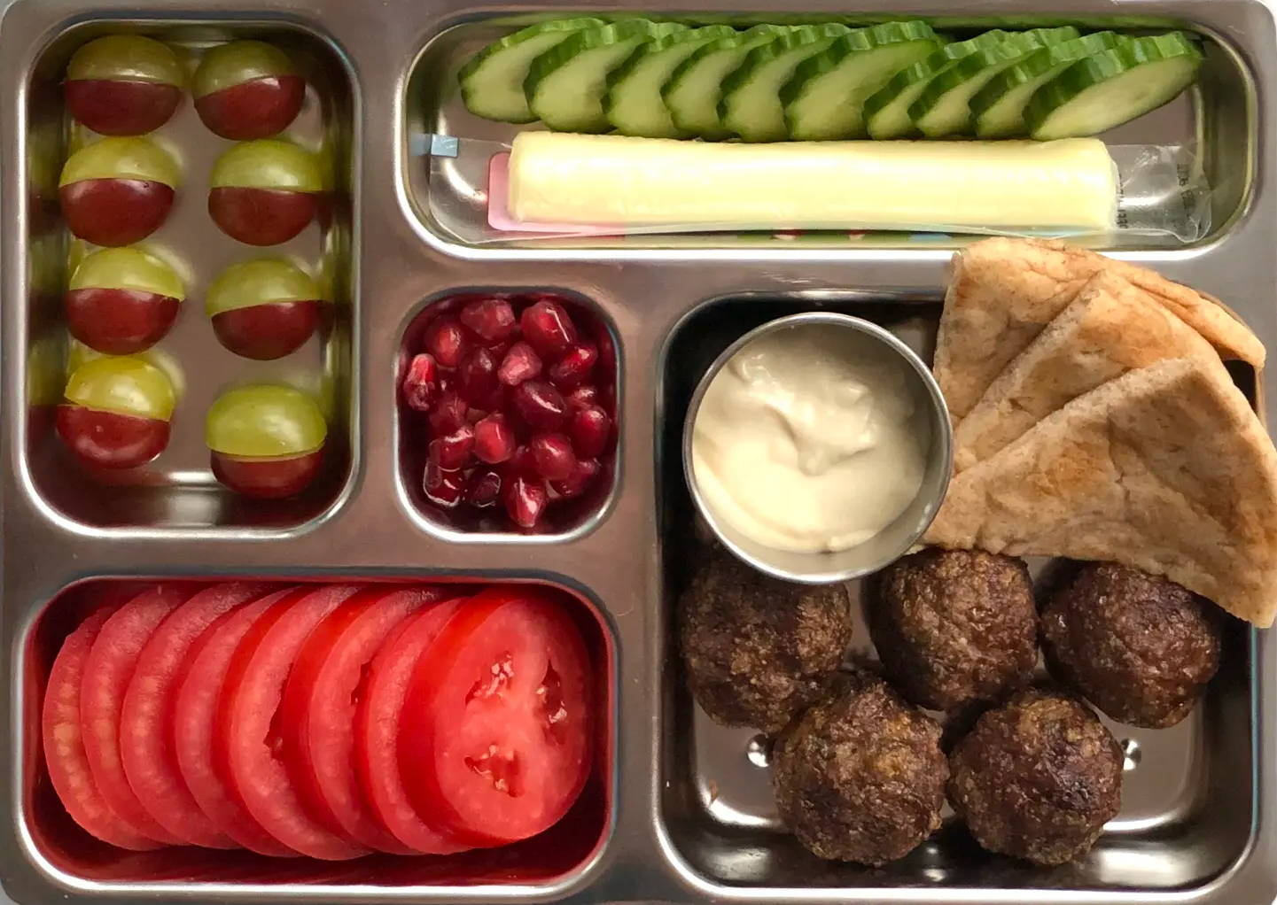 Sneak peek of a kid's quick and healthy school lunch containing  Beef Meatballs with Hummus & Pita, Sliced Tomatoes & Cucumbers, Cheese Stick, and Pomegranate Seeds.