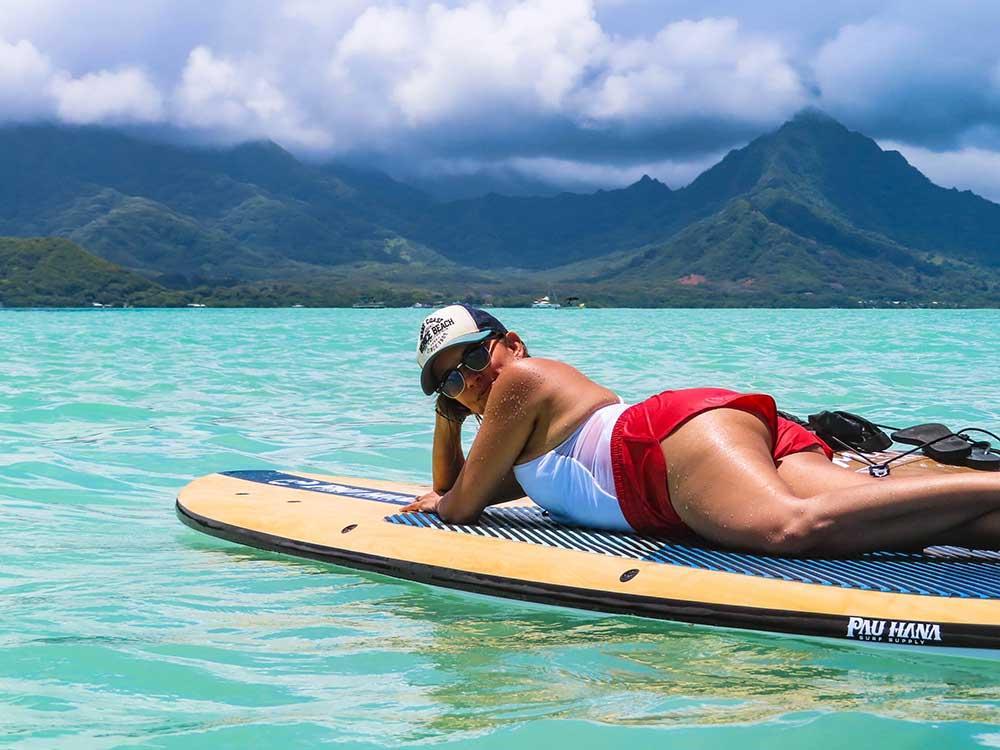 woman lying on the pau hana big ez hawaiian vft paddleboard