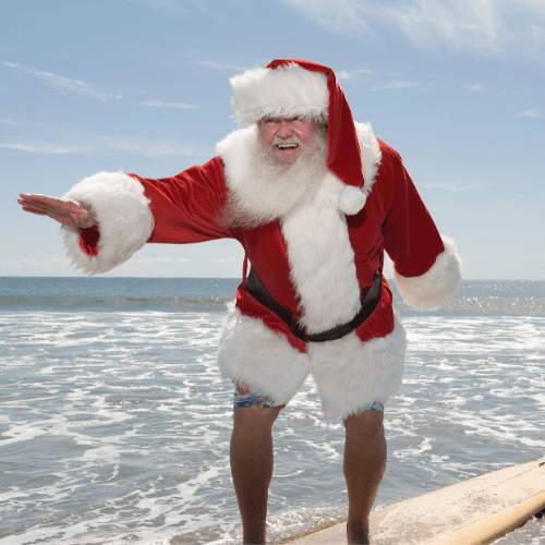 Surfing Santa Riding Surfboard in the Ocean