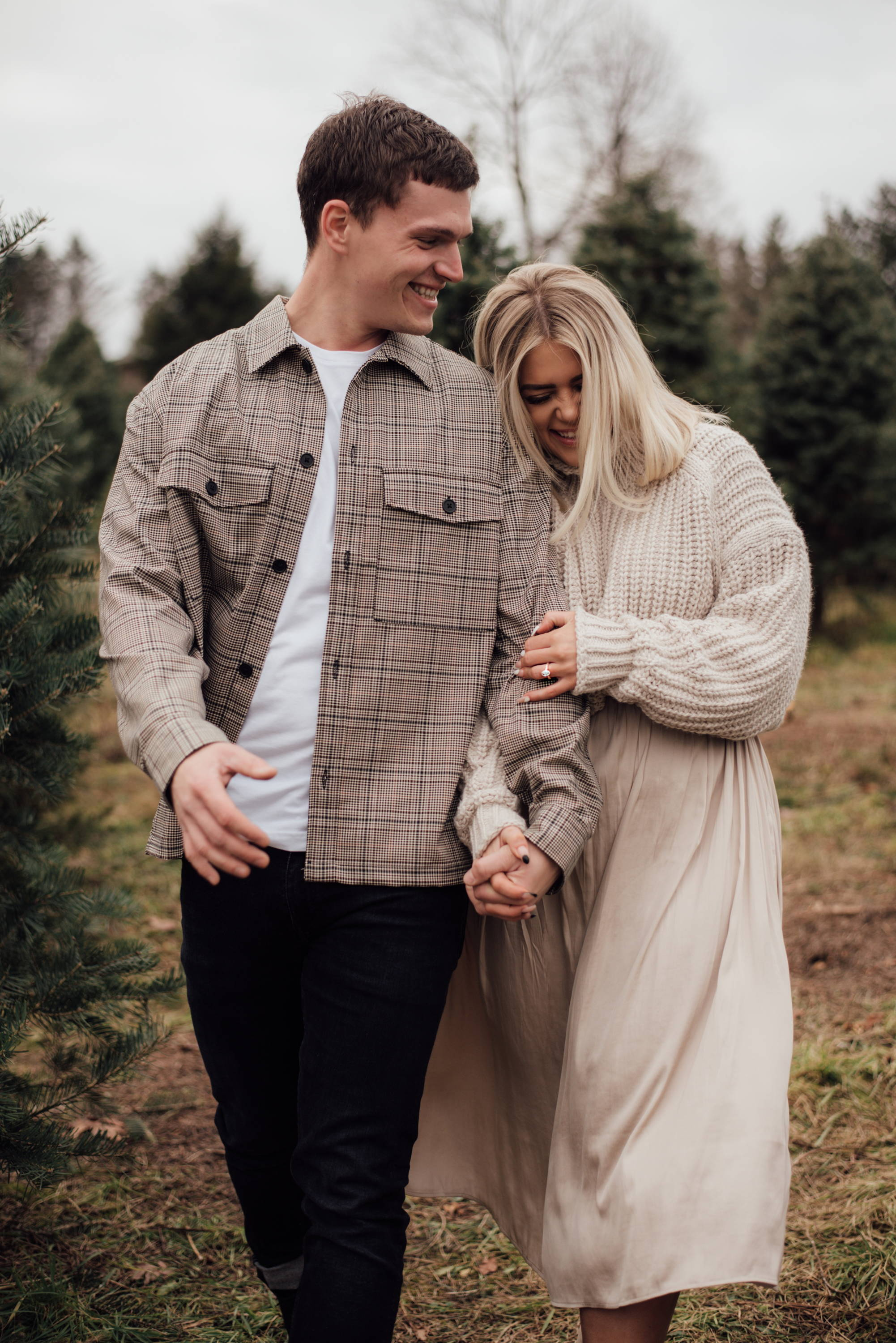 Henne Engagement Ring Couple James & Kelsey Smile and Laugh at a Christmas Tree Farm
