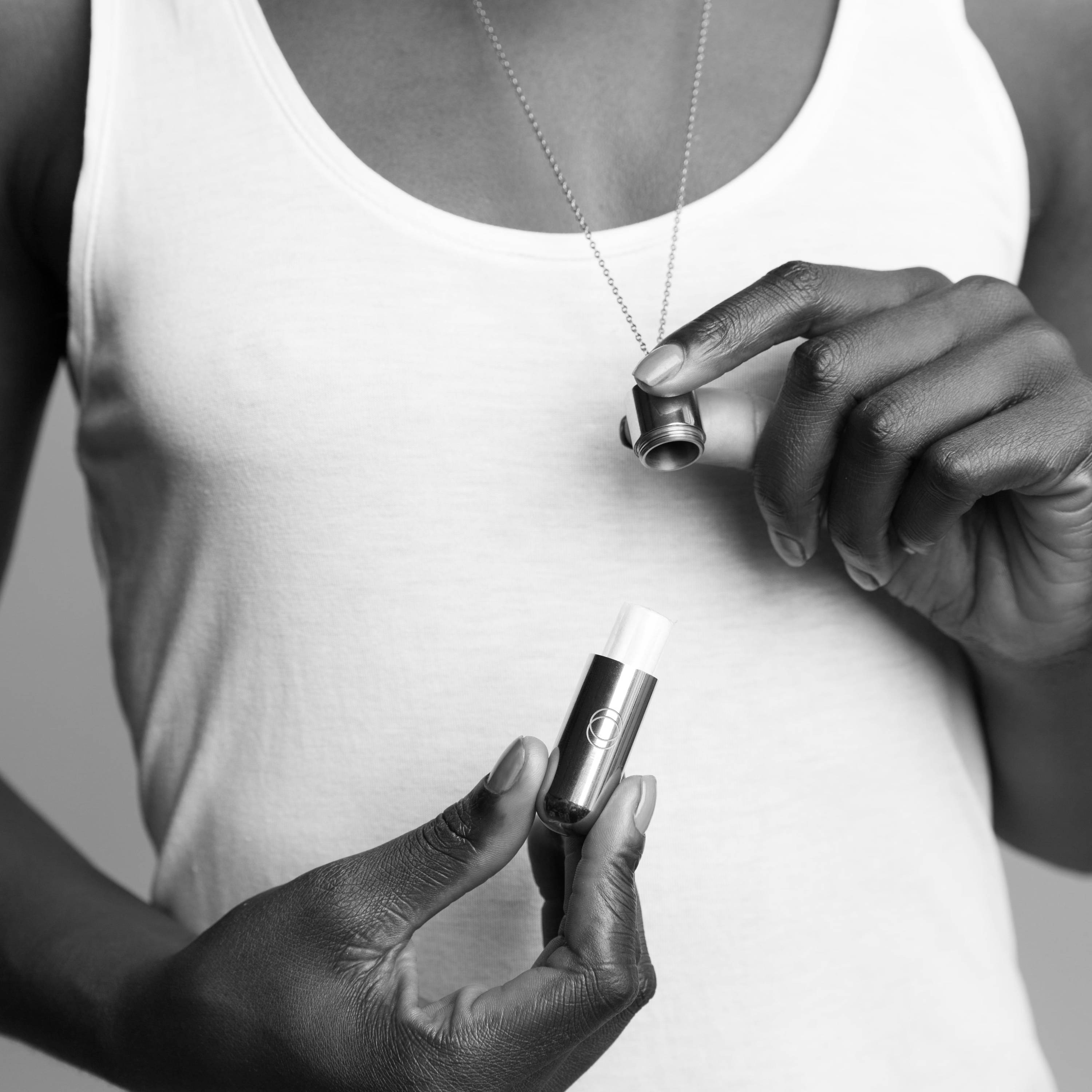 A woman holds an unscrewed Cora Fearless Necklace around her neck