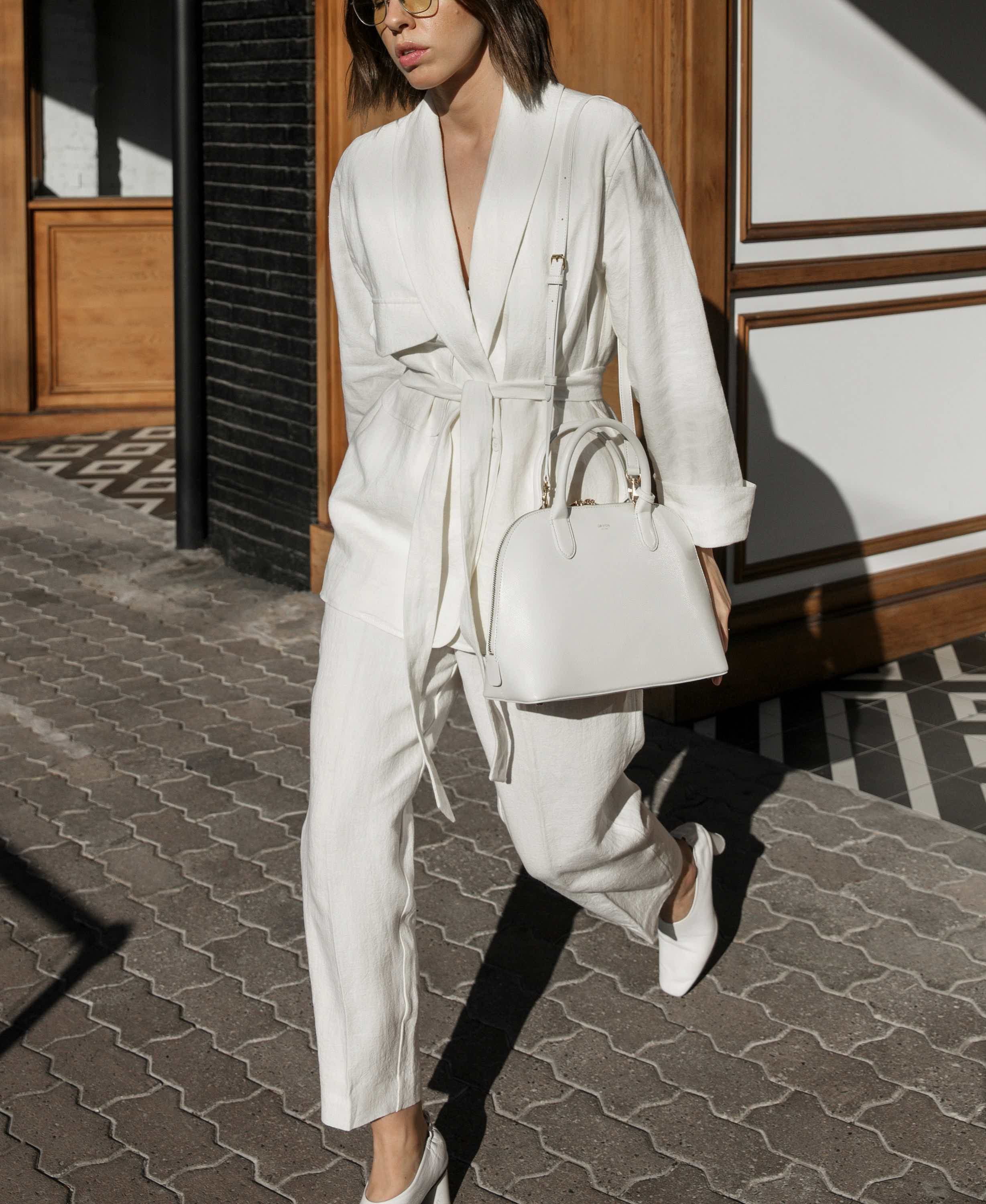 Kaity Modern in  an Oroton Linen Blazer with White grip top bag