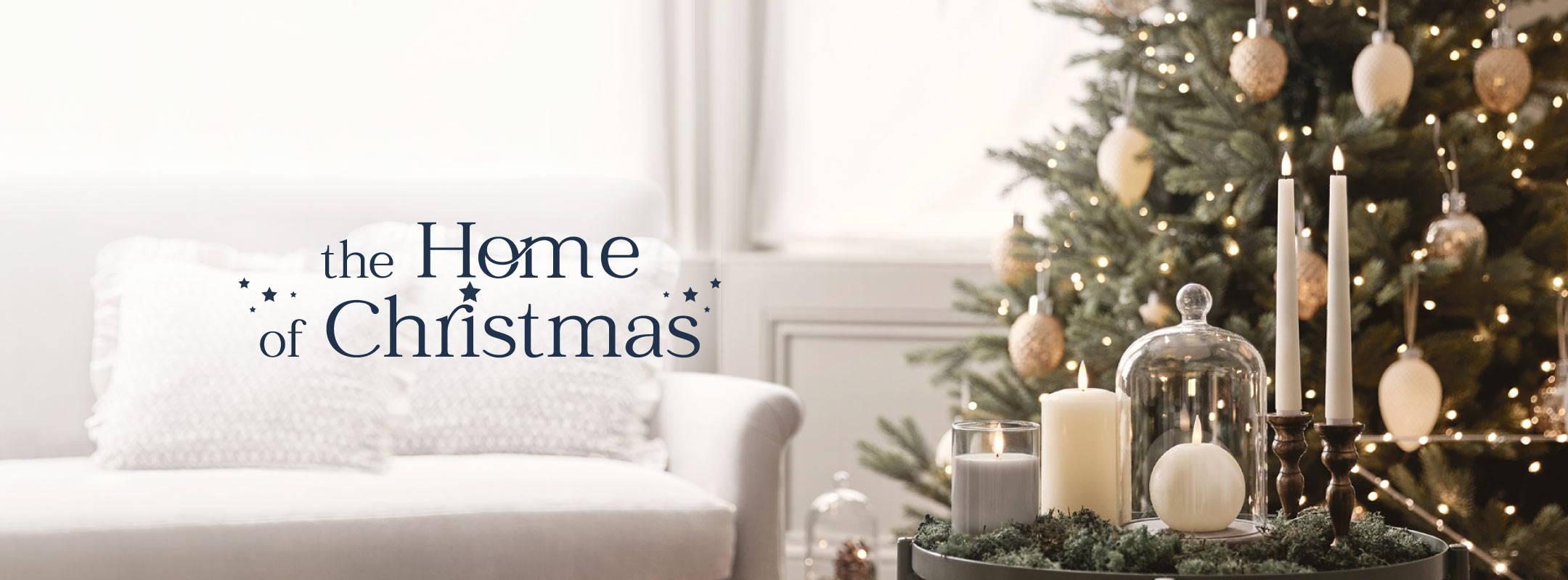 Verschiedene TruGlow LED Kerzen und eine Glasglocke auf einem Beistelltisch im Wohnzimmer, dahinter ein beleuchteter Weihnachtsbaum