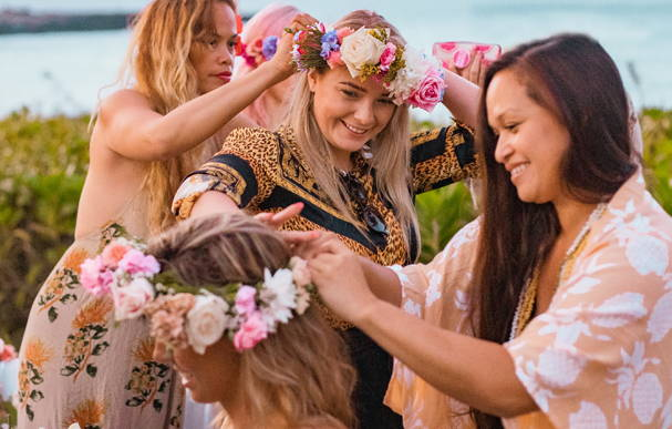 Ocean Dreamer (Pamakani Lehua Pico Purdy), pro surfer Sally Fizgibbons and sister Kawaila donning flower crowns at the Beachwaver Maui Pro Women's Surf Championships