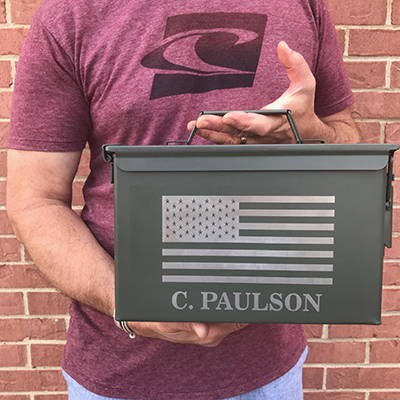 A man holding an engraved ammo box.