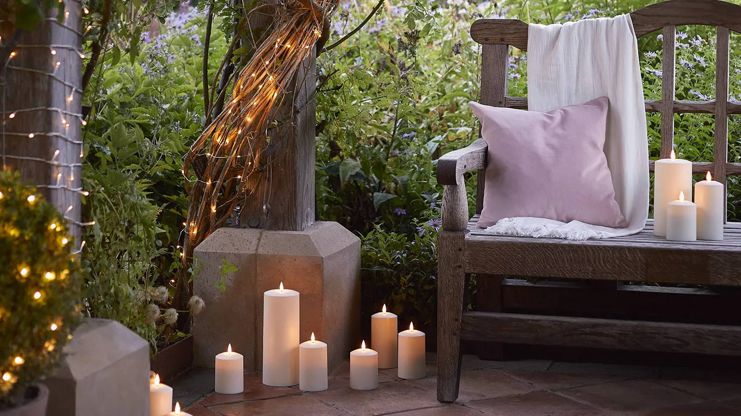 Courtyard setting with outdoor TruGlow candles and fairy lights illuminated