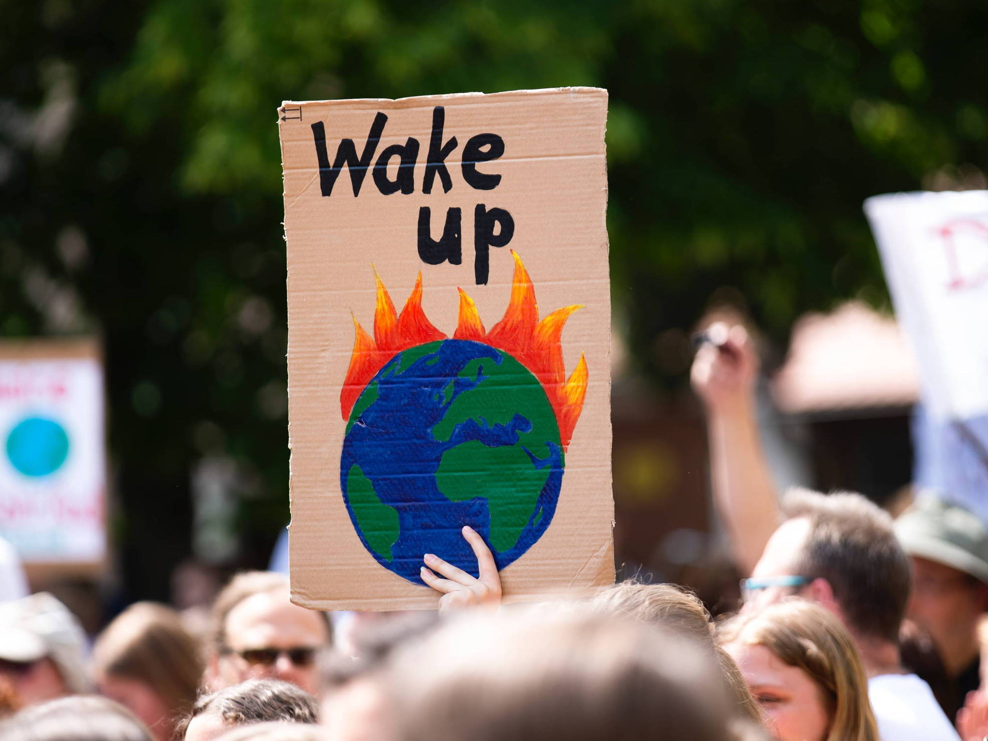 A protests holds up a sign with a painting of a burning planet and the words 'wake up'