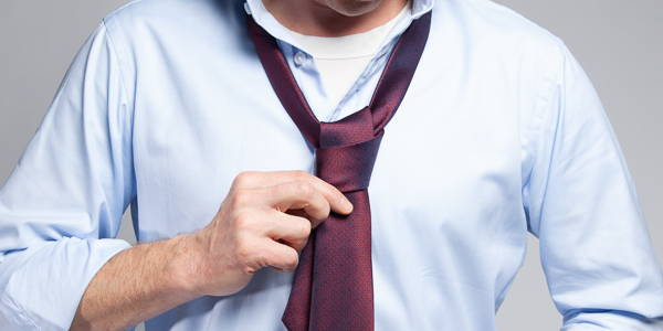 A picture of a man doing up his red tie showing a white crew neck undershirt under a blue shirt