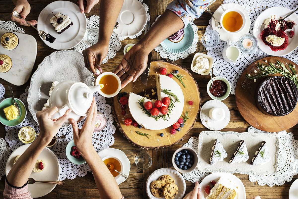 Table set for a tea party with a variety of desserts; hands pouring tea.