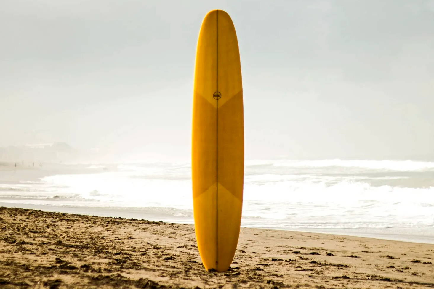 A yellow epoxy longboard standing up at the beach